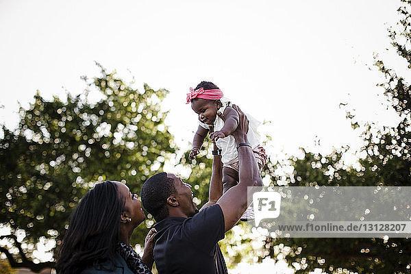 Niedriger Blickwinkel auf glückliche Eltern  die mit ihrer Tochter spielen  während sie im Park gegen den Himmel stehen