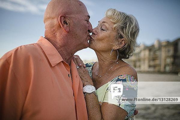 Romantisches Seniorenpaar küsst sich  während es am Strand gegen den Himmel steht