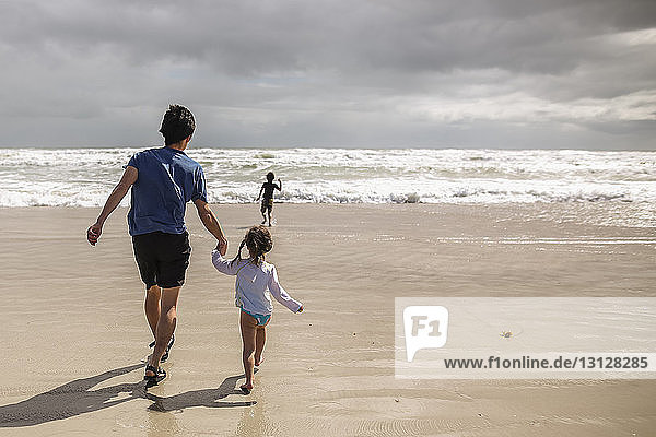 Rear view of father and daughter holding hands while son running towards sea on shore at beach
