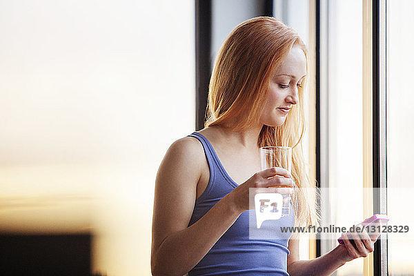 Junge Frau telefoniert  während sie zu Hause ein Glas in der Hand hält