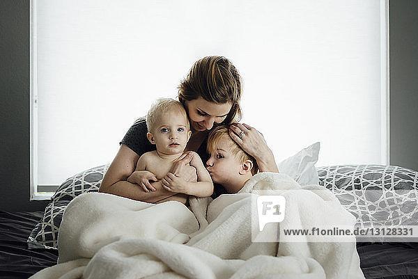 Mutter mit Söhnen zu Hause auf dem Bett sitzend