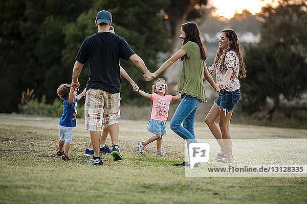 Familie spielt im Park Ringelreihen um den Rosenkranz