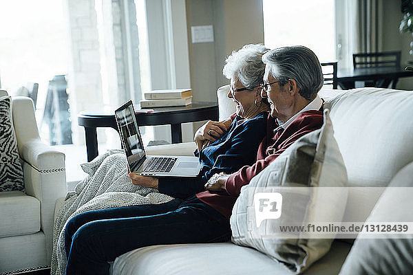 Happy senior couple video conferencing through laptop computer while sitting on sofa