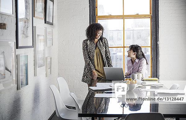 Lächelnde Geschäftsfrauen diskutieren im kreativen Büro