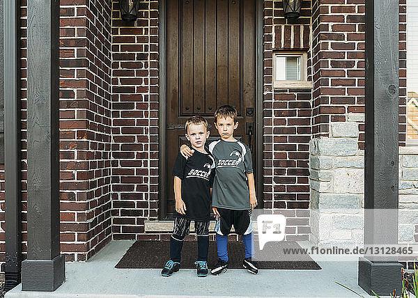 Portrait of boys standing against door