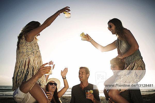 Fröhliche Männer tragen Freundinnen auf den Schultern  während sie sich am Strand vergnügen