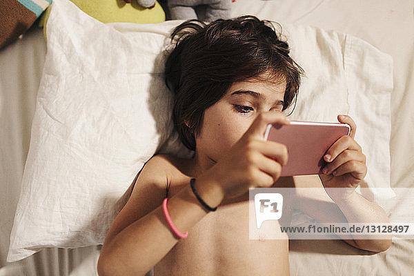 Draufsicht eines Jungen ohne Hemd  der ein Smartphone benutzt  während er auf dem Bett liegt