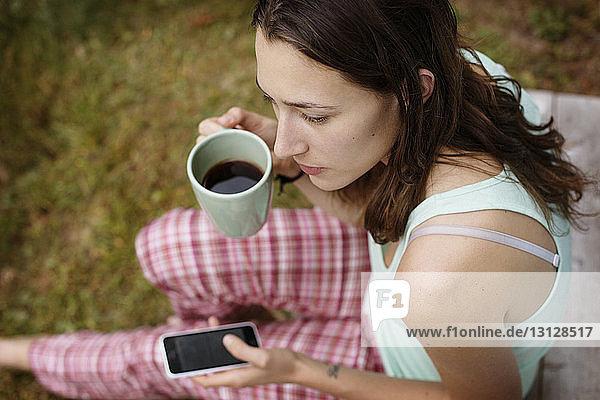 Schrägaufnahme einer jungen Frau  die auf dem Rasen sitzend eine Kaffeetasse und ein Smartphone hält
