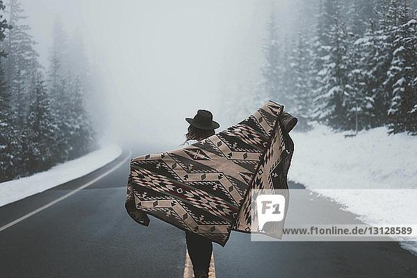 Rückansicht einer Frau mit Schal  die bei nebligem Wetter auf der Straße im Wald steht