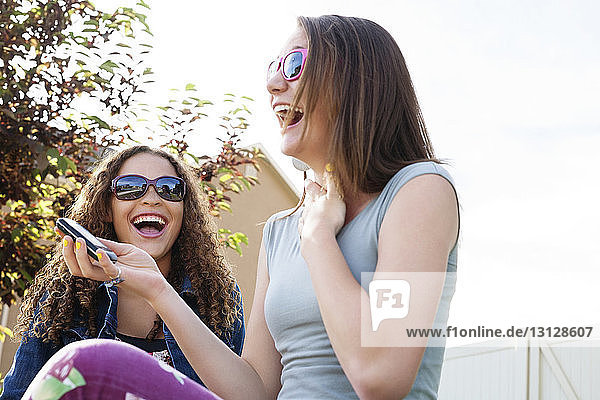 Low angle view of cheerful friends sitting against sky