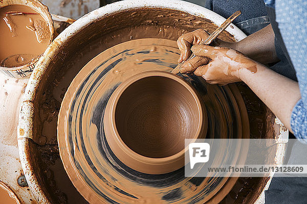 Cropped image of woman molding shape on pottery wheel