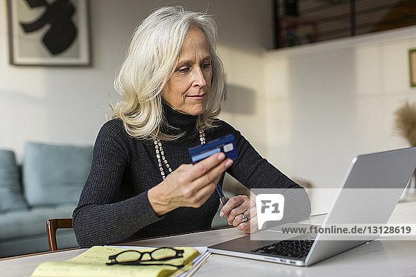 Ältere Frau benutzt Laptop-Computer beim Bezahlen von Rechnungen zu Hause