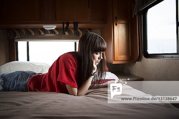 Young woman using smart phone while relaxing on bed in camper van