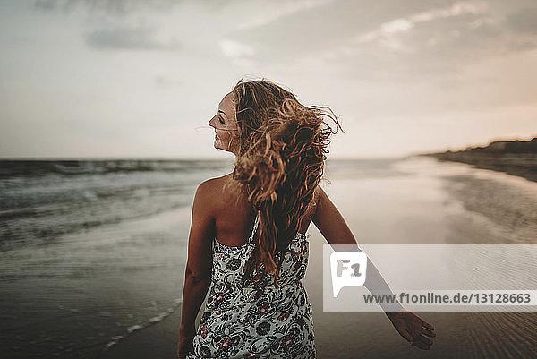 Rückansicht einer glücklichen Frau  die bei Sonnenuntergang am Strand gegen den Himmel läuft