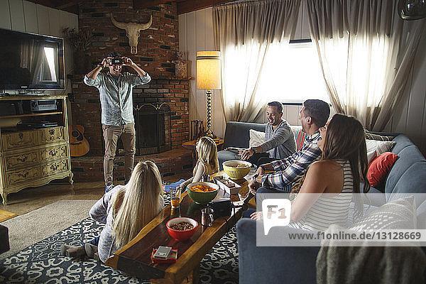 Glückliche Freunde schauen den Menschen an  während sie beim geselligen Beisammensein zu Hause ein Heads-up-Spiel spielen