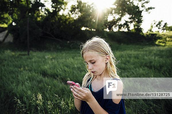 Mädchen benutzt Mobiltelefon  während sie auf einem Grasfeld steht