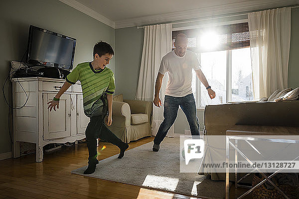 Father with son playing soccer at home