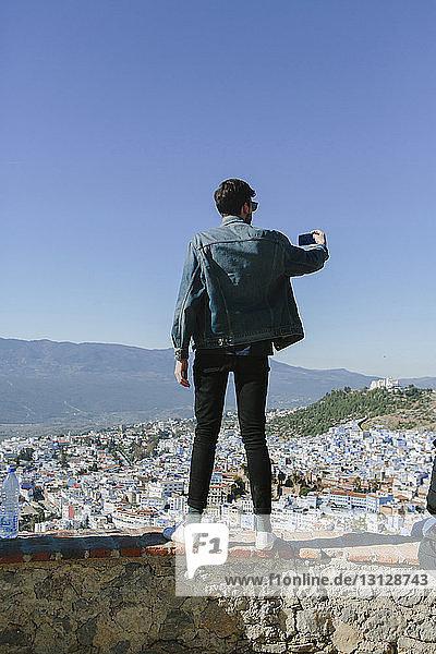 Rückansicht eines Mannes  der auf einer Stützmauer gegen das Stadtbild steht und dabei Selbstmord begeht