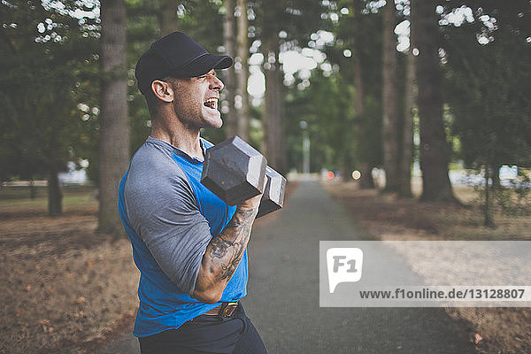 Side view of man screaming while lifting dumbbell while standing on road at park