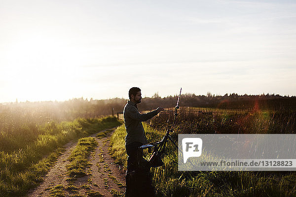 Side view of painter painting on canvas while standing at field against sky