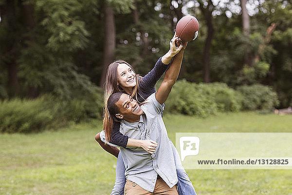 Man piggybacking woman while playing football on field