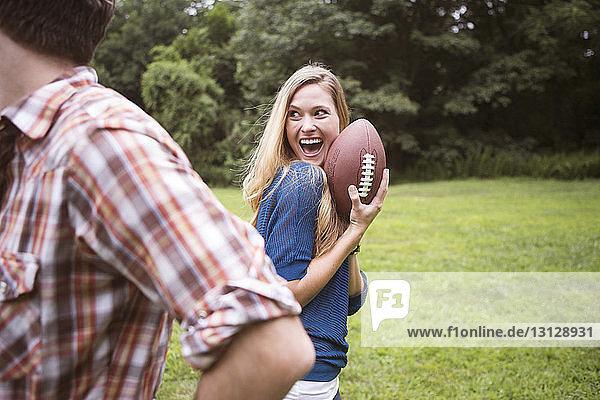 Fröhliche Frau hält Fussball in der Hand  während der Mann auf dem Rasenplatz steht