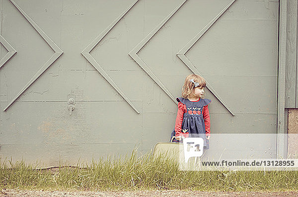 Girl holding suitcase while standing against wall