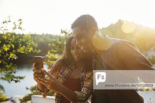 Couple taking selfie through smart phone at lakeshore during summer