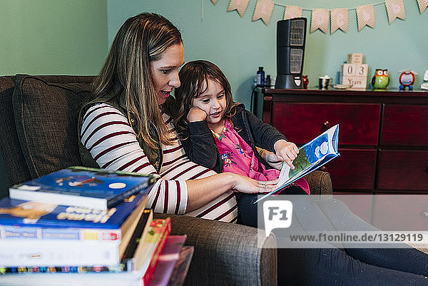 Pregnant mother with daughter reading book while sitting on armchair at home