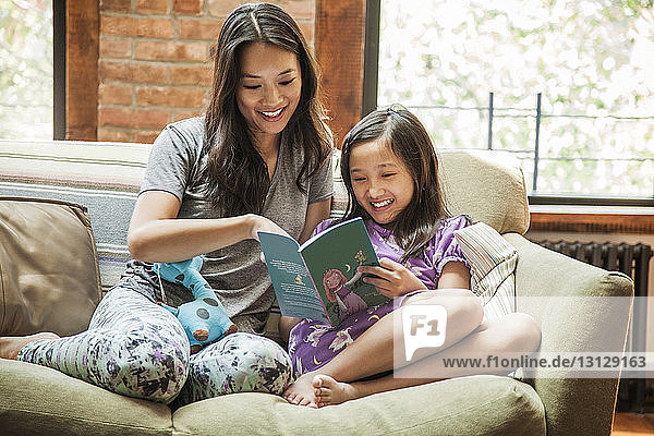 Mother and girl reading book while sitting on sofa at home