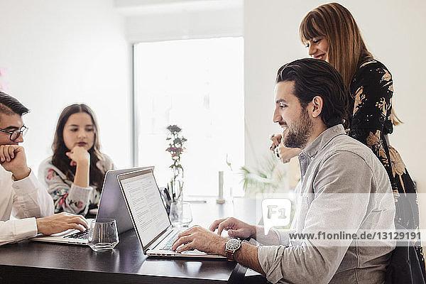 Geschäftskollegen mit Laptop-Computern am Schreibtisch im Büro