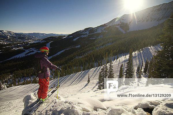 Seitenansicht eines auf einem Schneefeld stehenden Skifahrers