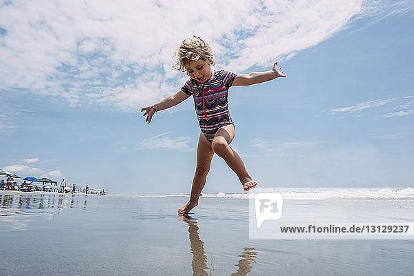 Niedrigwinkelansicht eines sorglosen Mädchens  das am Strand gegen bewölkten Himmel spielt