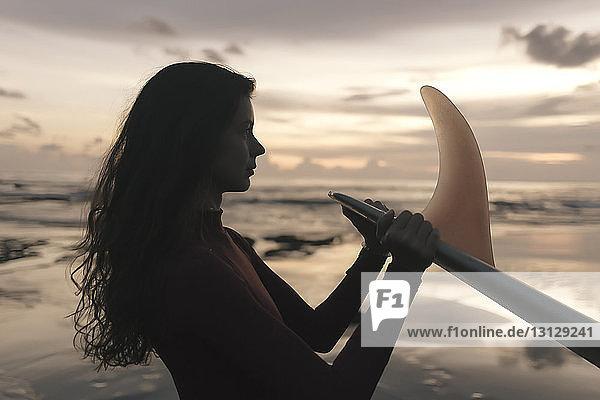 Seitenansicht einer nachdenklichen jungen Frau  die ein Surfbrett hält  während sie bei Sonnenuntergang am Strand gegen den Himmel steht Seitenansicht einer nachdenklichen jungen Frau, die ein Surfbrett hält, während sie bei Sonnenuntergang am Strand gegen den Himmel steht