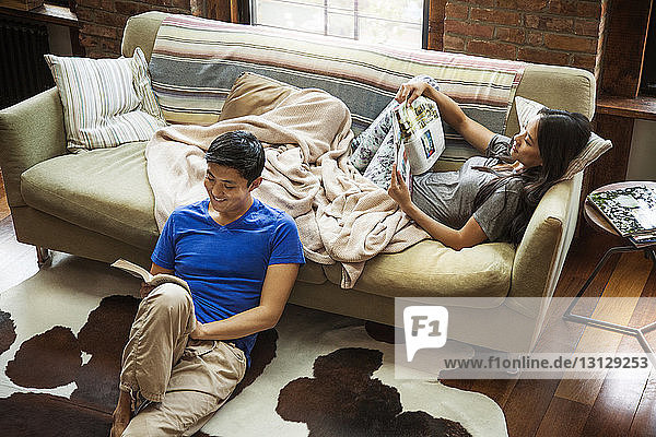 Couple reading book and magazine while relaxing at home