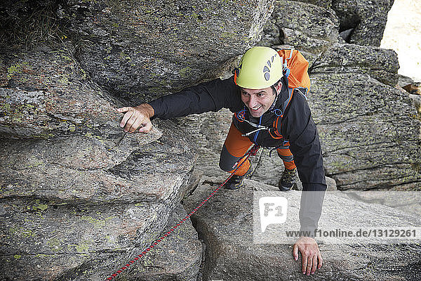 High angle view of smiling hiker clambering on rocks