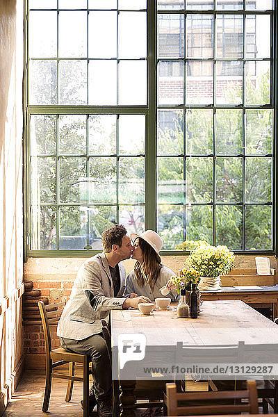 Küssende Paare am Tisch im Restaurant