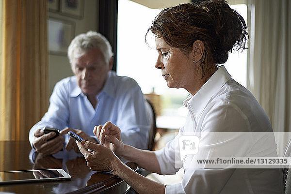 Ehepaar benutzt Mobiltelefon  während es am Tisch sitzt