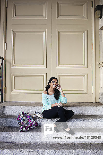 Woman talking on mobile phone while sitting on doorstep