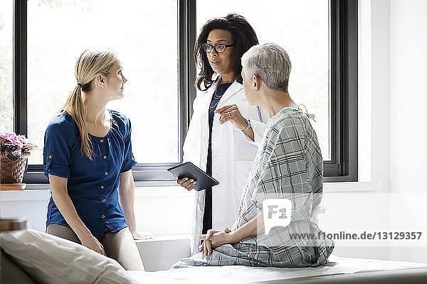 Arzt bespricht sich mit Frau und reifer Patientin im Krankenhaus