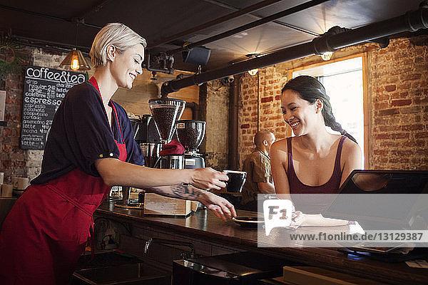 Seitenansicht einer Frau  die einem Kunden im Café Kaffee serviert