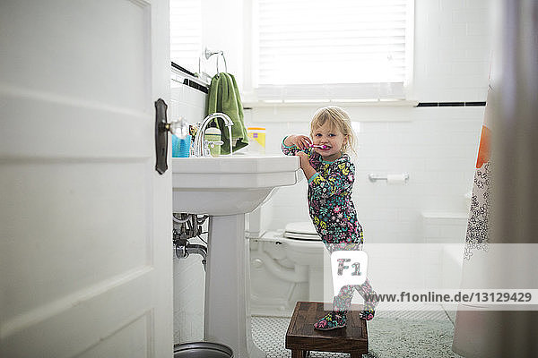 Portrait of cute baby girl brushing teeth while standing on stool in bathroom