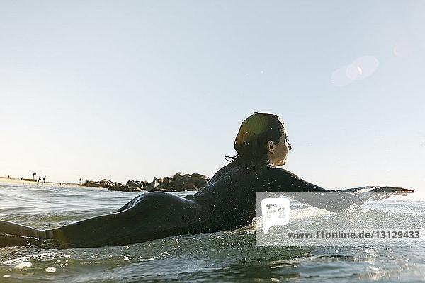 Side view of female surfer lying on surfboard in sea against clear sky