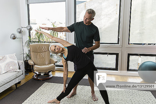 Man assisting woman practicing yoga at home