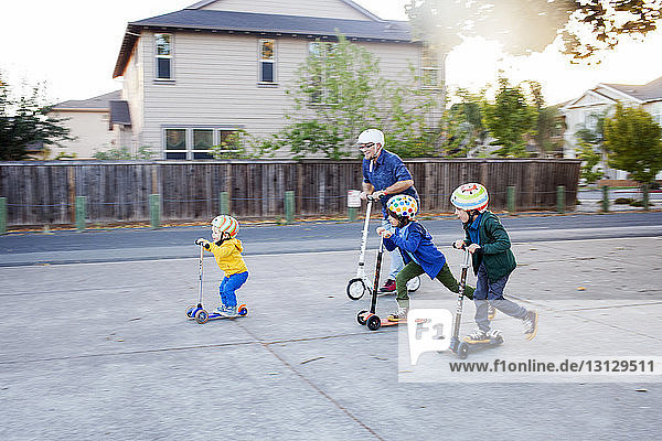 Father and sons enjoying with push scooter on street by houses