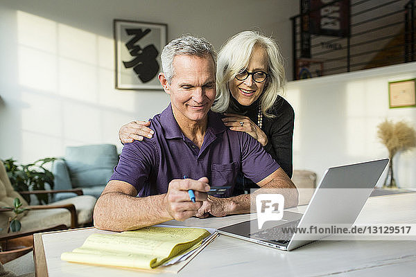 Smiling woman looking at laptop computer while man holding credit card in living room