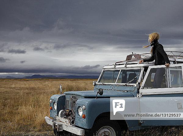 Weibliche Touristin betrachtet Aussicht  während sie im Geländewagen vor stürmischen Wolken steht