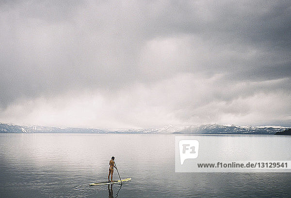 Woman paddleboarding on lake against cloudy sky
