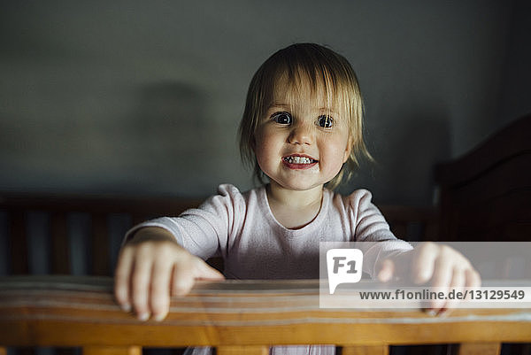 Portrait of smiling girl in crib at home