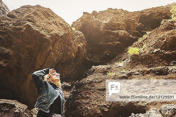 Reife Frau schaut auf  während sie gegen Felsen steht